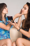 Two girls making up Stock Image