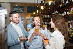 Two girls with man at bar Stock Images