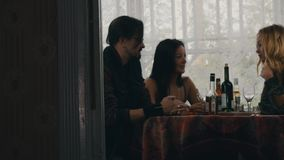 Two girls and man chat at table with alcohol drinks on terrace of country house stock footage