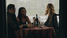Two girls and man chat at table with drinks on terrace of country house. Happy stock video footage