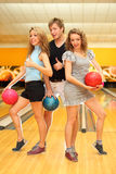 Two girls and man hold balls in bowling club Stock Image