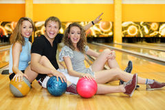 Two girls and man sit on floor with balls Stock Photo