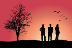 Two girls and man standing on hill near bare tree Royalty Free Stock Image
