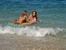 Two girls with matrass and baby toys on sea Stock Images