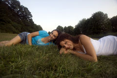 Two girls in meadow. Two early twenties caucasian females relax on a clear afternoon in a Connecticut, USA, meadow royalty free stock photo