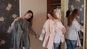Two girls measure clothes in front of a mirror. Two twin sisters measure the same jackets in front of the mirror in the bedroom. Choice of clothes. Two girls stock video