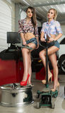 Two girls mechanic replace tires on wheels Royalty Free Stock Photography