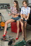 Two girls mechanic replace tires on wheels Stock Photo