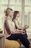 Two girls meditate in the office after work. Concept: work, relaxation, timeout Royalty Free Stock Image