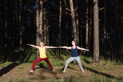 Two girls meditating practicing yoga fitness exercise at sunset in forest. Stock Photography