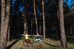 Two girls meditating practicing yoga fitness exercise at sunset in forest. Royalty Free Stock Photo