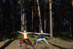 Two girls meditating practicing yoga fitness exercise at sunset in forest. Royalty Free Stock Image