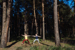 Two girls meditating practicing yoga fitness exercise at sunset in forest. Royalty Free Stock Photos