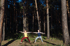 Two girls meditating practicing yoga fitness exercise at sunset in forest. Stock Photo