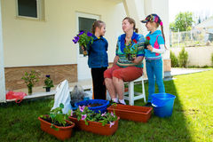 Two girls and a middle-aged woman engaged in planting flowers Royalty Free Stock Images