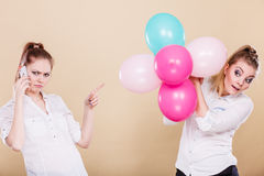Two girls with mobile phone and balloons Royalty Free Stock Photos