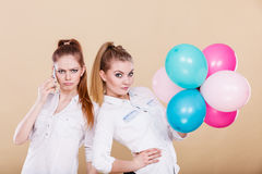 Two girls with mobile phone and balloons Royalty Free Stock Images