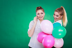 Two girls with mobile phone and balloons Royalty Free Stock Image