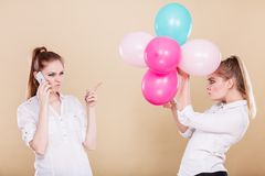Two girls with mobile phone and balloons. Two girls with colorful balloons and mobile phone. Best friends preparing party celebration, having problem, bad Royalty Free Stock Photos