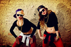 Two girls. Modern hip-hop dancers over brick wall. Urban lifestyle Royalty Free Stock Image