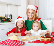 Two girls with mother baking Christmas cookies in the kitchen Stock Photos