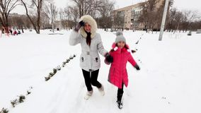 Two girls, mother and daughter, walking park in winter frosty day. stock footage