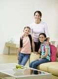 Two girls and mother in living. Two young girls and mother in living room with backpacks Stock Photos