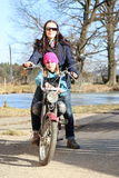 Two girls on a motorbike. Young women driving a motorbike with a little girl - smiling child Royalty Free Stock Photo