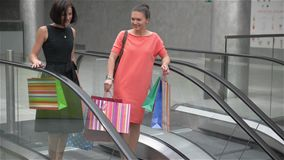 Two girls moving down the stairs on escalator in shopping mall, friends are shopping in a store, women making purchases. Two girls moving upstairs on escalator stock footage