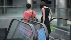 Two girls moving down the stairs on escalator in shopping mall, friends are shopping in a store, women making purchases stock video