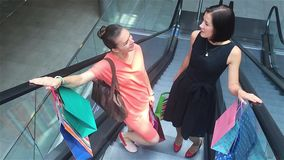 Two girls moving upstairs on escalator in shopping mall, friends are shopping in a store. Laugh stock video