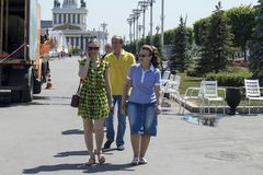 Two girls in multi-colored dresses are walking along the avenue of the VDNH park. Moscow, RUSSIA - June 5, 2019 Two girls in multi-colored dresses are walking stock photos
