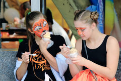 Two girls with narisoval tiger mask on his face eating ice cream Royalty Free Stock Image
