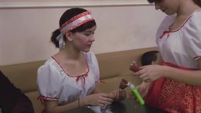 Two girls in national costumes glue parts of paper. Scissors, paper, markers on table. Handmade stock footage