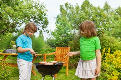 Two girls near BBQ grilling meat in the garden Royalty Free Stock Photography