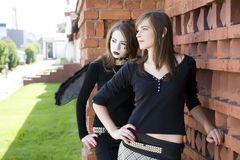 Two Girls Near A Brick Wall Royalty Free Stock Photography
