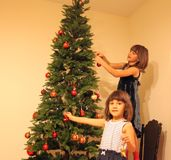 Two girls near Christmas tree. Two girls decorate Christmas tree stock photography
