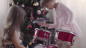Two girls near christmas tree playing drum kit Royalty Free Stock Photos
