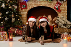 Two girls near the fireplace and Christmas tree Royalty Free Stock Photo