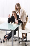 Two girls near the glass. Table Royalty Free Stock Image