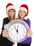 Two girls in New Year's caps with clock Stock Photo