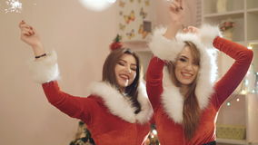Two girls in new year's suits dancing with the sparkles indoor in 4K.  stock footage