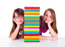 Two girls next to book column Stock Photos