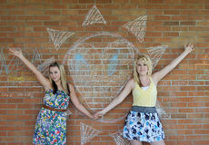 Two girls next to a heart Royalty Free Stock Photos