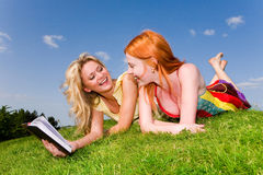 Two girls with notebook on the green grass. Two beautiful girls with notebook outdoors. Lay on the green grass Royalty Free Stock Photo