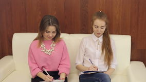 Two girls with a notebook in hands on master class stock video