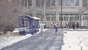 Two girls with numbers run on straight line in snow day. Slow motion. Contest stock footage