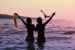 Two girls in ocean. Ilhouettes of girls in the ocean at sunset Royalty Free Stock Images