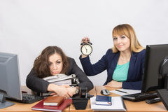 Two girls in the office at the end of the day, one with a smile, holding a clock, another weary lies on folders Stock Image