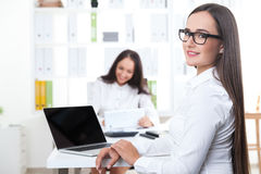 Two girls in office with gadgets stock images